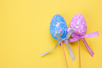 Easter holiday background. Pastel coloured decorated easter eggs on a bright yellow background