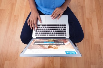 Composite image of mid section of female executive using laptop