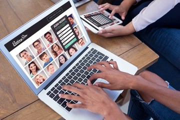 Composite image of executives using digital tablet and laptop at