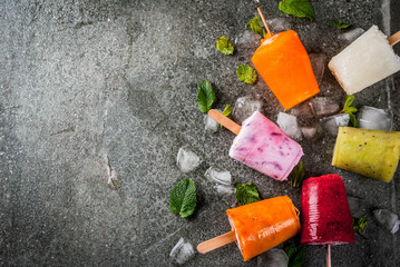 Healthy summer desserts. Ice cream popsicles. Frozen tropical juices, smoothies blueberries. currants, orange, mango, kiwi, banana, coconut, raspberry. On black stone table, copy space top view