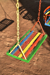 multi-color painted swing for child on playground