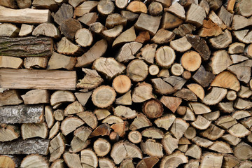 A lot of dry chopped firewood is stacked in the period of preparation for the furnace chopped logs for winter fire