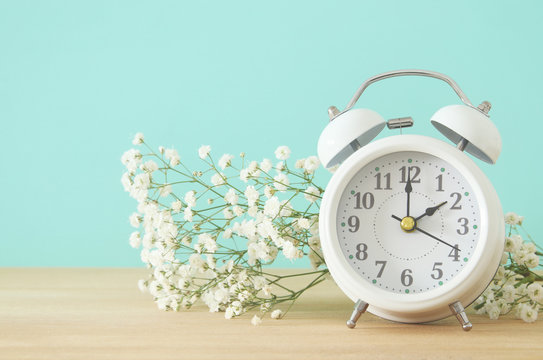 Image of spring Time Change. Summer back concept. Vintage alarm Clock over wooden table.