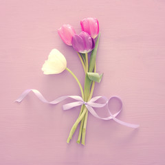 bouquet of pink and white tulips over white wooden background. Top view.
