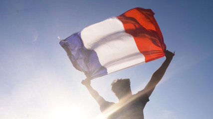 Young man holding french national flag to the sky with two hands at the beach at sunset france