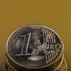 stack of coins is one euro. Euro money. Dark background.