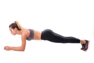 Concentrated beautiful fitness girl in sportwear exercising doing plank over white background