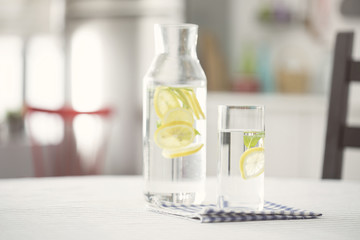 Water bottel and glass of water with lemon in kitchen