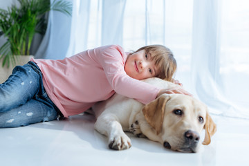 Happy kid  with down syndrome and Labrador retriever cuddling on the floor