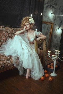 Beautiful model wearing white lace dress is posing in a dark studio