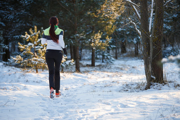 Picture from back of young athlete walking through winter forest