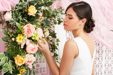 Photo from back of young brunette in white dress on background of flowers