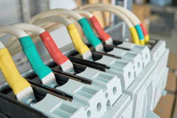 Power circuit breakers are arranged in a row in an electric Cabinet. Cables or marked wires are connected to the switches. Focus on the front switch. The marking is red, green and yellow.