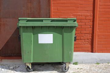 green garbage bin on the street