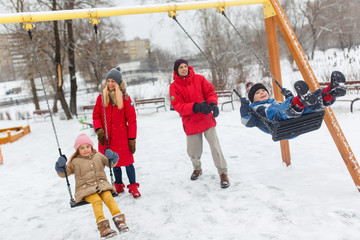 Photo of happy girl and boy swinging in winter in park with parents