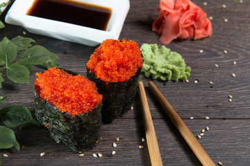 Tobiko-flying fish roe sushi. Japanese rice roll with seaweed at sushi bar