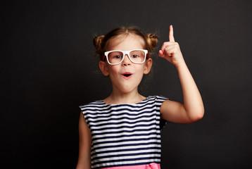 Child having idea. Pretty girl in glasses posing with finger up over blackboard.
