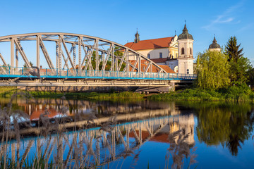 View at bridge over the Narew river and baroque Church in Tykocin town, Podlasie, Poland