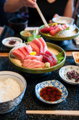 Fresh salmon, tuna, toro, maguro, otoro sashimi with wasabi on ceramic plate on dinner table