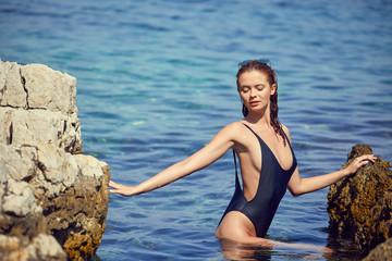 portrait of happy wet young woman in white bikini standing in sea water