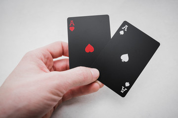 Gambling. Two aces in hand in black colored playing cards