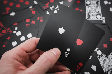 Gambling. Two aces in hand in black colored playing cards background