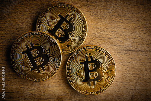Three Virtual Shiny Coins Bitcoins Heap On Dark Wooden Background Close Up Of