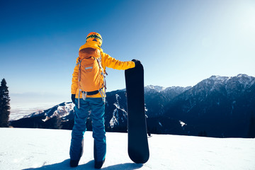successful snowboarder with snowboard on winter mountain top