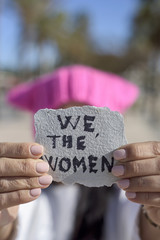 woman with a pink hat and the text we the women
