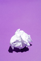Creased sheet of white paper on violet background
