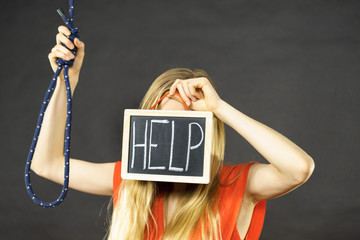 Suicidal woman holding help sign next to rope