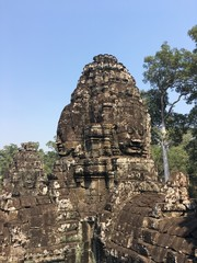 Angkor Wat in Siem Reap, Cambodia. Stone faces carved in the ancient ruins of Bayon Khmer Temple