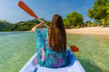 Young woman paddling a canoe along the shore of an idyllic islan