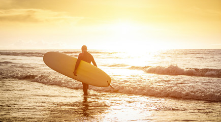 Wall Mural - Guy surfer walking with surfboard at sunset in Tenerife - Surf long board training practitioner in action - Sport travel concept with sof focus water near feet - Warm sunshine color foltered tones