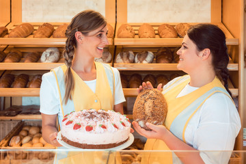 Sales women in bakery with cake and bread showing them to the customer