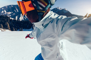 one snowboarder taking selfie while snowboardingon winter mountain top slope