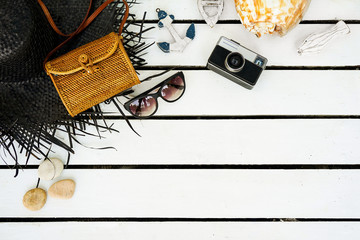 Minimal styled flat lay isolated on white wood background. Feminine desk top view with summer accessories: hat, sunglasses, vintage photo camera, handbag, shell, anchor, boat, stones, fish