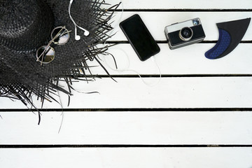 Minimal styled flat lay isolated on white wood background. Feminine desk top view with summer accessories: hat, sunglasses, vintage photo camera, headphones, smartphone.Holiday travel app presentation