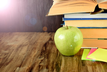 Pile of textbooks and a green apple on a wooden table. Copy space