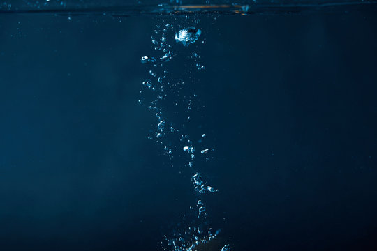 full frame of dark water with bubbles background