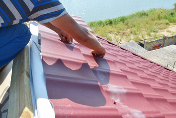 Roofing construction. Roofer installing metal roof sheets on the house rooftop.