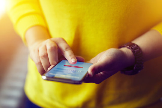Woman signs up to banking with her mobile phone in the office