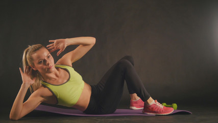 Sportive blonde woman in sports clothing is training press muscles