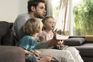 Father and children blowing into sails of toy model ship on couch at home