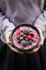 Girl holding bowl with overnight oats with frozen berries