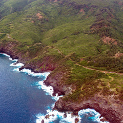 Aerial view of Maui's coastline, surf, and the Kahekili highway in Hawaii, shot from a small, low-flying prop plane