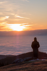 Woman on mountain Schoeckl looking over low stratus to sunset