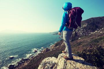 hiker stand on sunrise seaside mountain cliff edge
