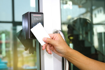 Close-up hand inserting keycard to lock and unlock door