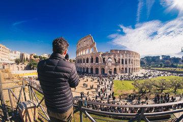 Tourist taking pictures at the Colosseum in Rome, Italy